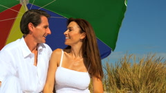 Couple Sitting Under Beach Parasol Stock Footage