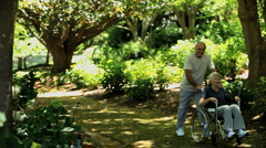 Man strolling with his wife in a wheelchair Stock Footage