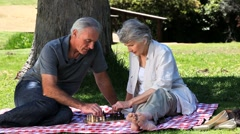 Elderly couple playing chess on a tablecloth Stock Footage