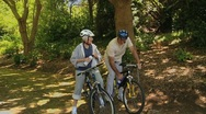 Old man and woman drinking and biking Stock Footage