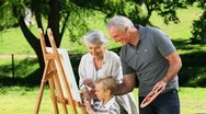 Young boy painting a canvas with grandparents Stock Footage