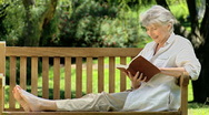 Elderly female reading a book sitting on a bench Stock Footage