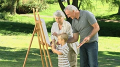 Boy painting a canvas with his grandparents Stock Footage