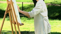 Old woman painting a white canvas in the Park Stock Footage