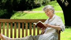 Senior woman reading a book sitting on a bench Stock Footage