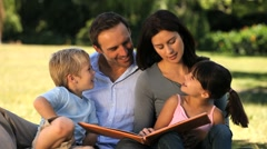 Family reading a book sitting on the grass Stock Footage