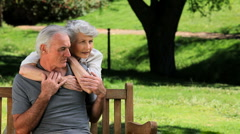 Senior woman hugging her man sitting on a bench - stock footage