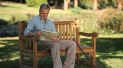 Senior man reading a book sitting on a bench Stock Footage