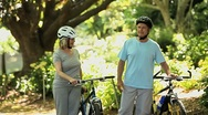 Elderly couple walking and pushing bikes Stock Footage