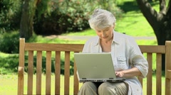 Elderly female looking at a laptop sitting on a bench Stock Footage