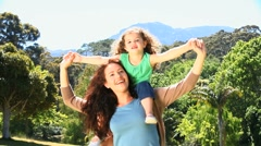 Woman carrying her daughter on his shoulders Stock Footage