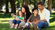 Family enjoying time together sitting on the grass Stock Footage