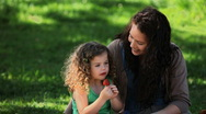 Mom and daughter enjoying strawberries sitting on the grass Stock Footage