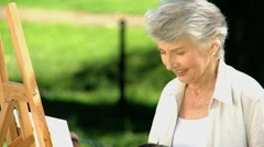 Old female painting a canvas Stock Footage