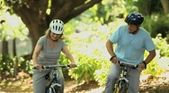 Old man and woman biking together Stock Footage