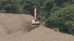 Digger building floodbank moves forward. Stock Footage