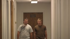 2 guys walking down a hall at work - stock footage