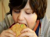 Young boy eating hamburger Stock Footage