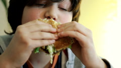Young boy eating hamburger - stock footage