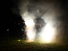 A lot of small fireworks explosions on grassy lawn Stock Footage