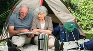 Stock Video Footage of Seniors looking at a map sitting front of a tent