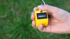 Hand of boy using hand-held tally counter against grass Stock Footage