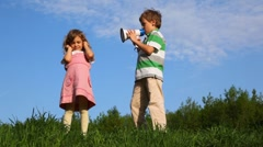 Boy talking through megaphone with little girl plugging up her ears outdoor Stock Footage