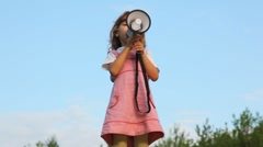 Little girl standing on hill and talking through megaphone Stock Footage