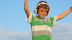 girl and boy listen to music in headphones - stock footage