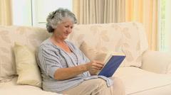Old woman reading a book and smiling at the camera Stock Footage