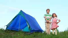 Boy and little girl having joines hands stands near tent Stock Footage