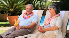 Aged couple relaxing on deckchairs Stock Footage