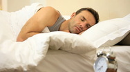 Man looking at the alarm in the bed Stock Footage