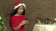 Stock Video Footage of Asian Elf With Santa Hat Listens To Christmas Music