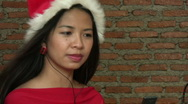 Stock Video Footage of Asian Girl With Santa Hat Listens To Christmas Music