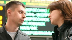 Couple stands against indicator board in railroad station and talks Stock Footage