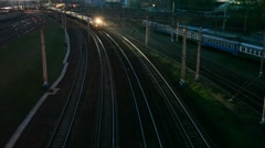 Suburban electric train moving on night railway near station Stock Footage