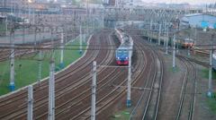 Suburban electric trains moving on railway lines near station Stock Footage