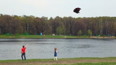 Boy and little girl with kite in bat form on bank of river Stock Footage