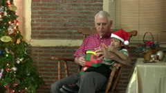 Grandfather Opens Christmas Gifts With Grandson Stock Footage