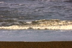 Closer shot of waves lapping up to an English beach near Cromer Stock Footage