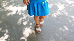 Legs of little girl follow chamber by ground Stock Footage