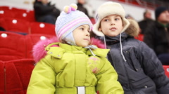 Girl and boy sit on armchairs, attentively watch hockey match Stock Footage