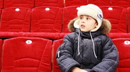 Boy sits in armchair, attentively watch hockey match Stock Footage