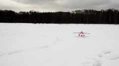 Toy radio-controlled plane flies up from snow Stock Footage