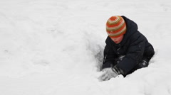 Boy sits among snow and builds of it wall Stock Footage