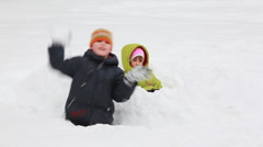 Little girl and boy sit among snow, he throws it to chamber in winter morning Stock Footage