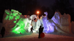 Snow sculptures of dinosaurs in late evening at artificial color illumination Stock Footage