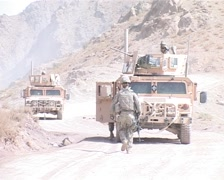 Humvees on top of mountain patrolling Afghanistan Stock Footage