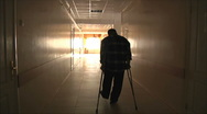 Stock Video Footage of man goes to the hospital corridor on the crutches